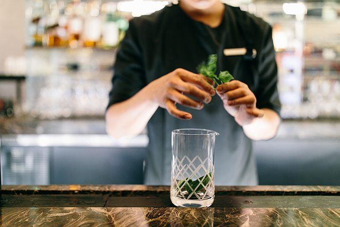A bartender adds basil to the Green Negroni at Charlie Palmer at the Knick.